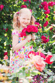 Happy girl with roses in garden — Stock Photo