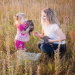 Little girl and mother with cats outdoor — Stock Photo