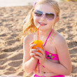 Little girl drinks orange juice outdoor — Stock Photo #23379574
