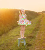 Happy girl on chair outdoor — Stock Photo