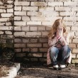 Girl on background brick wall — Stock Photo