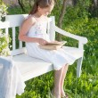 Royalty-Free Stock Photo: Smiling girl with open book is sitting on the wooden bench in spring garden