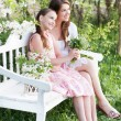 Happy mother with daughter in spring garden — Stock Photo