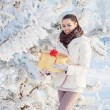 Girl with gift in winter park — Stock Photo