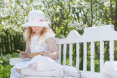 Smiling girl with open book is sitting on the wooden bench in spring garden — Stock Photo