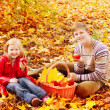 Children with apples in autumn park — Stock Photo