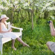 Mother photographing her daughter at spring garden — Stock Photo
