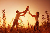 Happy family outdoor, silhouettes on sunset — Stock Photo