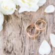 Wedding rings on wooden background — Stock Photo