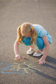 The child drawing a chalk on asphalt — Stock Photo
