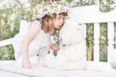 Little girl with toy on white wooden bench — Stock Photo