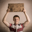 Young man holding wooden table — Stock Photo
