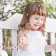 Stock Photo: Little girl on white wooden bench