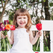 Stock Photo: Happy girl with tulips on white wooden bench