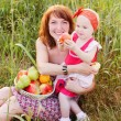 Happy mother and child with fruits outdoor — Stock Photo