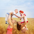 Two mothers with children in field — Stock Photo