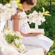 Girl with book in garden — Stock Photo