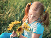 Little girl with sunflowers — Stock Photo