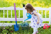 Girl watering spring flowers — Stock Photo