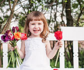Happy girl with tulips on white wooden bench — Stock Photo