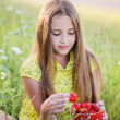 Happy girl with strawberry outdoor — Stock Photo