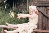 Little girl with flowers on wooden bench — Stock Photo