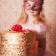 Little girl in festive dress with gift and carnival mask — Stock Photo