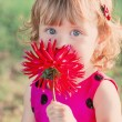 Little girl wit red dahlia outdoor — Stock Photo