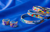 Enamel earrings and bracelet on blue cloth — Foto Stock