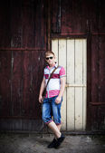 Young man standing next to a wooden wall outdoors — Stock Photo