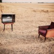 TV and chair in summer field — Stock Photo