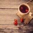 Stock Photo: Cup of tea with hip roses, on wooden table
