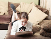 Beautiful pre-teen girl with tablet pc indoor — Stock Photo