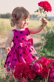 Little girl with flowers outdoor — Stock Photo