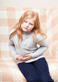 Child with stomach ache in sofa — Stock Photo