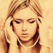 Beautifu blonde womwith pearl beads — Stock Photo #39186907