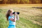 Girl looking through binoculars outdoor — Stock Photo