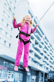 Happy girl jumping on background building — Stock Photo