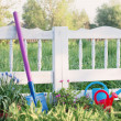 Painted white picket garden fence with watering can and shovel — Stock Photo