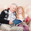Stock Photo: Grandfather and granddaughter sitting on sofand reading bo