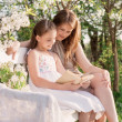 Happy mother with daughter with book in spring garden — Stock Photo