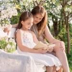 šťastná matka s dcerou, s knihou v jarní zahradě — Stock fotografie