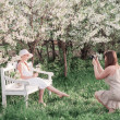 Stock Photo: Mother photographing her daughter at spring garden