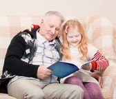 Grandfather and granddaughter sitting on the sofa and reading bo — Stock Photo