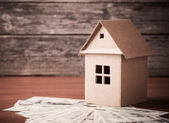 House from the paper and money on wooden background — Stock Photo