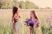 Two adorable girl with flowers outdoor — Stock Photo