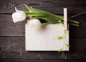Paper attach to rope with clothes pins and tulips  on wooden bac — Stock Photo