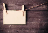Old paper attach to rope with clothes pins on wooden background — Stock Photo