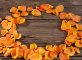 Orange roses petals on wooden table — Stock Photo