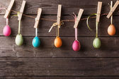 Easter eggs attach to rope with clothes pins on wooden backgroun — Stock Photo